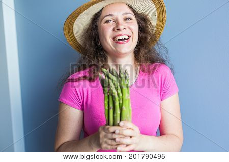 Close-up portrait of funny surprised woman is holding asparagus in front of her face.