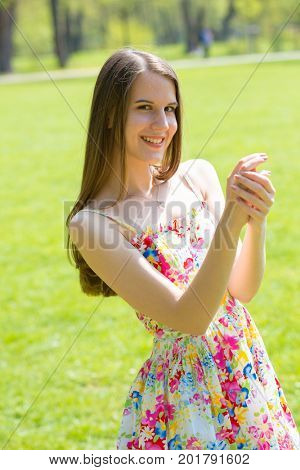 Portrait of young beautiful woman with long hair wearing flower dress in green spring park
