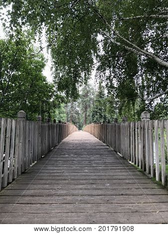 Hanging tree branches drape over a wooden footbridge leading to Drake Park in Central Oregon on a summer afternoon.