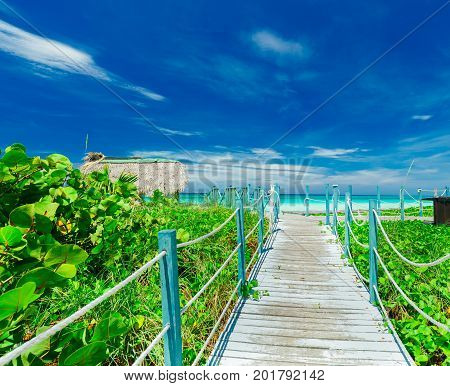 nice amazing view from the wooden bridge leading to a white sand beach and tranquil turquoise ocean at Cayo Coco island, Cuba