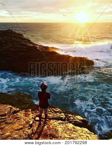 Boy looks at sunset over a rocky coastline. Quiberon, Britanny, France.