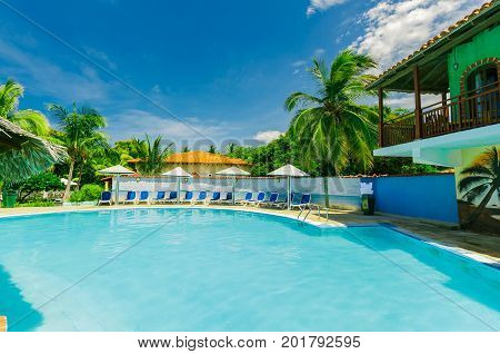 Cayo Coco island, Cuba, Colonial hotel, July 16, 2017, stunning gorgeous amazing view of Colonial hotel grounds, beautiful inviting swimming pool and retro stylish buildings on blue sky background