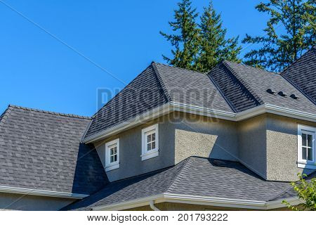 A perfect neighborhood. Houses in suburb at Summer in the north America. Top of a luxury house with nice window over white clouds in the blue sky.