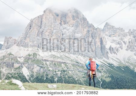 Female mountaineer with backpack, helmet and harness with climbing gear enjoying stunning view to mount Tofana di Rozes before ascent during summer day in Dolomite Alps - adventure concept