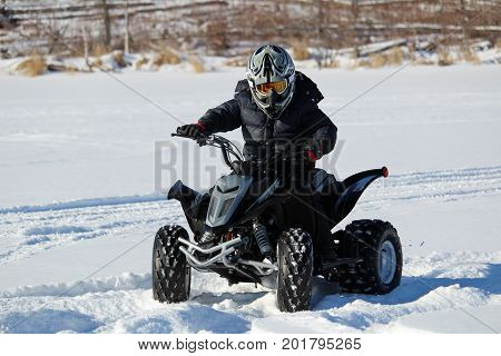 A boy riding a quad during the winter.