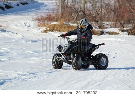 Child With His Quad in Winter with trees in the background