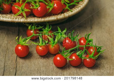 Fresh cherry tomato on wood basket. Close up lovely cherry tomato for background or wallpaper. Prepare fresh cherry tomato for home cooking look so delicious. Side view selective focus on foreground. Cherry tomato for vegetable concept.