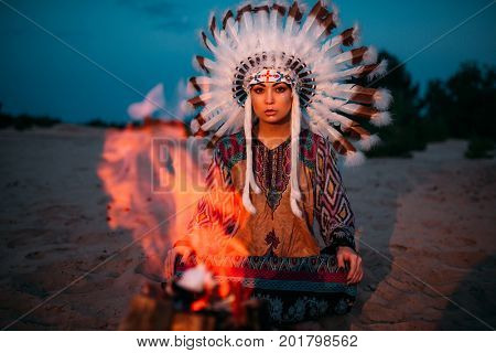 American Indian girl against bonfire, shaman