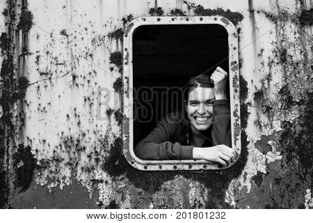 Black and white portrait of attractive young woman looking out of the window metal caboose.