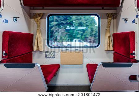Interior of a modern Thai economy class train interior. Modern train comfortable colorful chairs. Contemporary train interior. Empty seats.