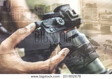 Double exposure of man holding a mirrorless camera with the city of Recife, Pernambuco, Brazil.
