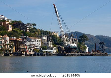 A tall dredger working in San Francisco Bay very near land and homes on a steep hillside. The dredge is on a raft  with tires lining the entire side.