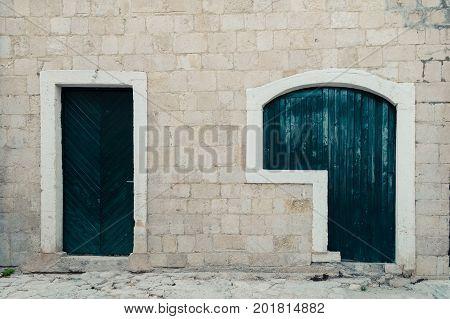 Stone wall with green wooden doors in Stari Grad of Ulcinj Montenegro.