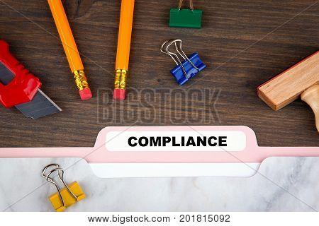 compliance concept. Folder Register on a dark wooden desk.