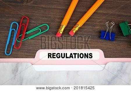 regulations concept. Folder Register on a dark wooden desk.