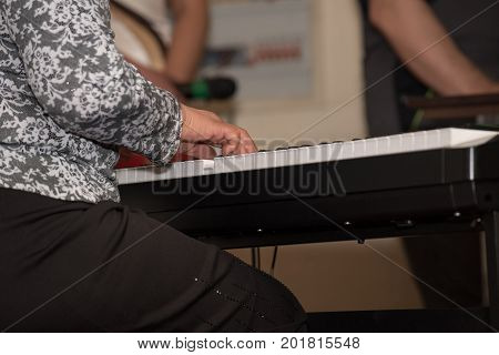 The hands of an adult woman in a black skirt are playing on the synthesizer on stage
