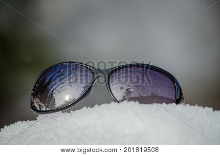 Sunglasses with black lenses and a reflection of the nature of them lie on the snow
