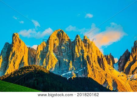 The Dolomites, Tirol. Magnificent serrated cliffs illuminate the summer sunset. The concept of eco-tourism in Alpine meadows