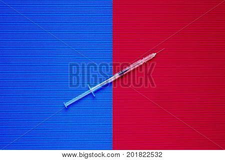 Medical syringe. Syringe for insulin on red and blue background