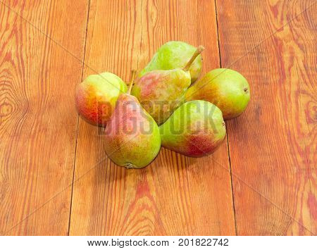Several ripe red and green European pears on a surface of an old dark wooden planks