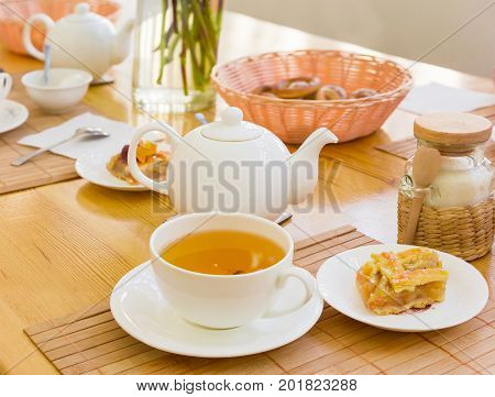 White cup with a herbal tea and a piece of cake on a saucer on the bamboo napkin on a background of a teapot and other tea appliances