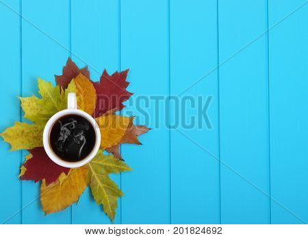 Autumn leaves, hot steaming cup of coffee  on wooden blue background.