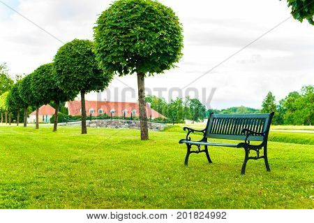 Ancient bench in royal green garden of Rundale Palace in Latvia. Multicolored outdoors summertime horizontal image.