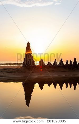 Beach with sandcastles on spectacular Baltic sea sunset background in Latvia. Multicolored summertime outdoors vertical image with filter. Copy space.