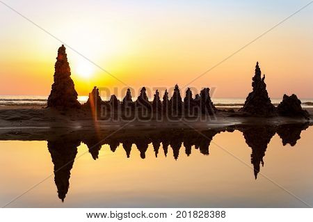 Beach with sandcastles on spectacular Baltic sea sunset background in Latvia. Multicolored summertime outdoors horizontal image with filter. Copy space.