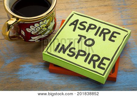 aspire to inspire reminder  or advice - handwriting in black ink on a sticky note with a cup of coffee