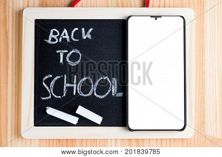Back to school written on a blackboard with bezel less smart phone and chalk. Traditional vs modern learning abstract concept.