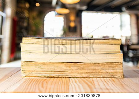Pile of books on a desk with classroom background. Traditional education concept.