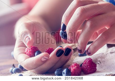 bog whortleberry raspberries and female hands with black and pink art manicure on a sackcloth