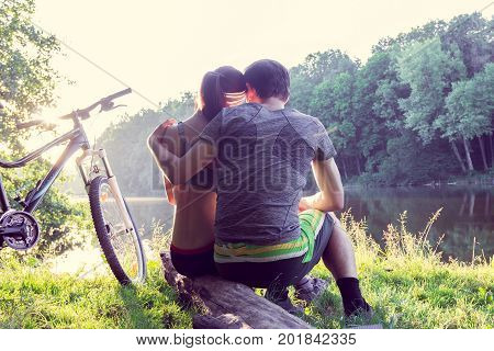 couple is embrace each other sits on the river bank with bicycle
