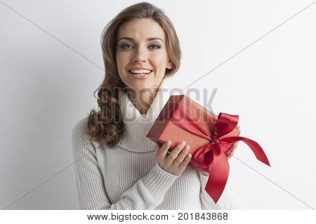 Cute young blond woman in white winter sweater holding red gift box, christmas, new year gift