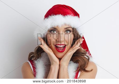 Christmas woman. Beauty model girl in Santa Hat. Funny Surprised Woman Portrait. Open Mouth. True Emotions. Red Lips and Manicure. Beautiful Holiday Makeup