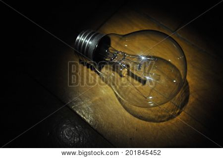 Closeup Antique Vintage Edison Style Light Bulb Against Dark Background. Light In Dark Room