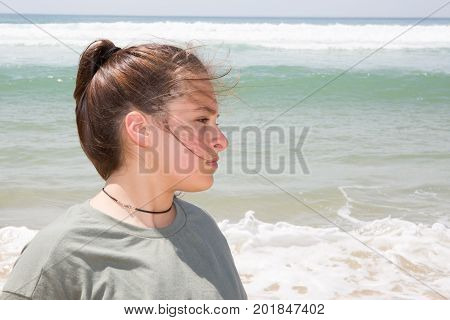 Woman On In Sand Beach Looks Thoughtfully Into Distance To Last Ray Of Sunset, Falling On Hectic Sea
