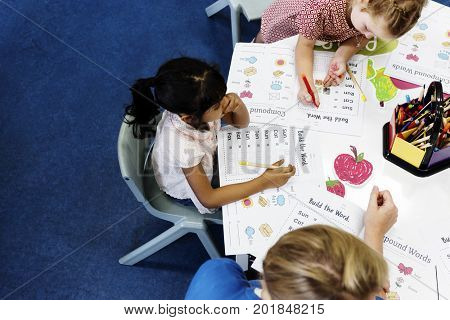Group of diverse Kids coloring workbook in class