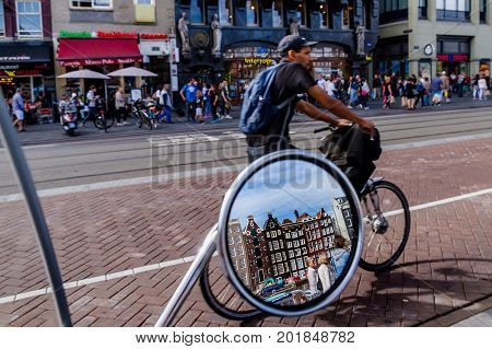 AMSTERDAM NETHERLANDS - 27 JULY 2017: Reflection of historic houses in the mirror of a scooter parked in the center of Amsterdam.