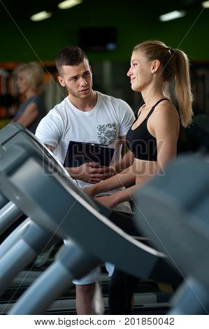 Happy smiling female working with personal trainer in gym. Young beautiful woman exercising on treadmill with assistance of fitness coach. Healthy lifestyle, fitness and sports concept.