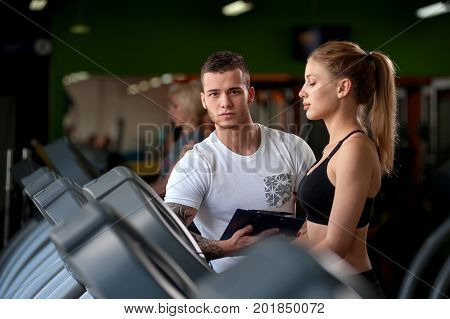 Young male personal trainer with female client in modern fitness center. Beautiful blonde woman working out on treadmill with the assistance of coach. Healthy lifestyle, fitness and sports concept.