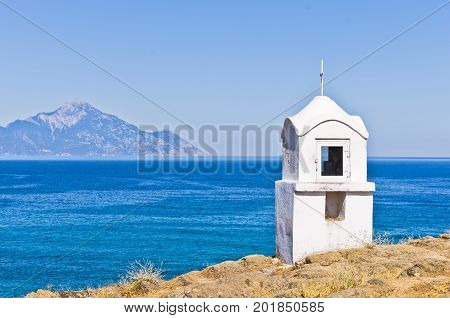Small white church or chapel with holy mount Athos in background, Greece