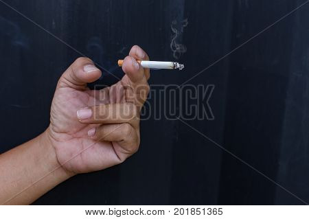Hand with smoking,Close up cigarette or tobacco with smoke in hand and copy space