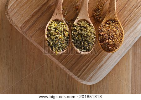 Various Spices Spoons On Wooden Table. Top View With Copy Space