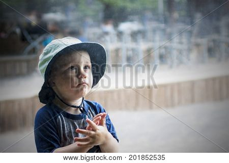 Cute toddler prays under the rain outdoor. Kid is praying to god asking him for help with folding hands for prayer and worship