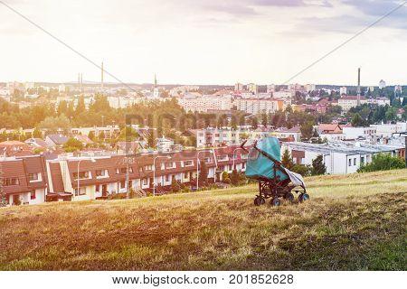 Abandoned baby in stroller in huge city. Baby sleeps in stroller alone on field