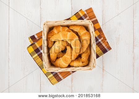 Basket with freshly baked homemade croissants on wooden background top view