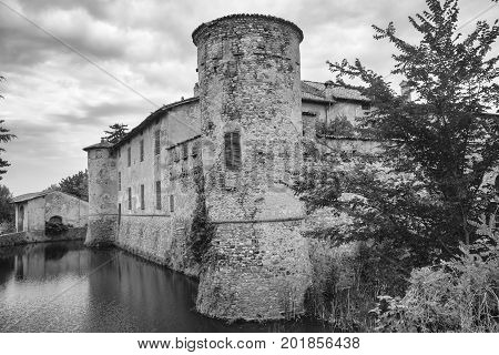 Lisignano (Piacenza Emilia Romagna Italy): the historic castle near Agazzano with waterlilies in the moat water. Black and white