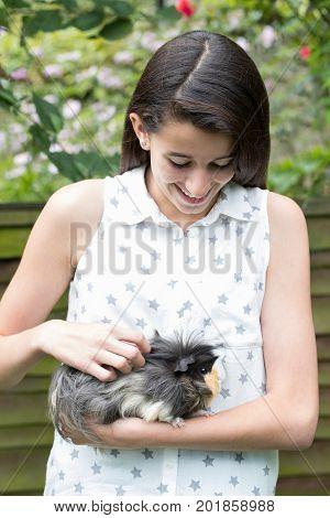 Girl In Garden Looking After Pet Guinea Pig